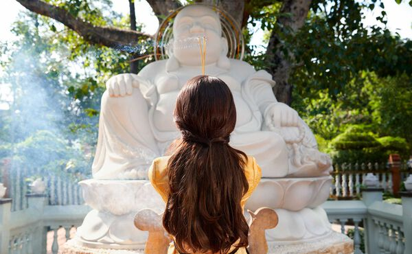 Woman who is meditating in front of buddha